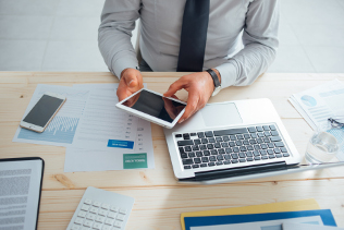 Professional businessman working at desk and using a touch screen tablet, technology and communication concept